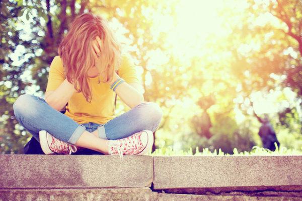 Teenage girl feeling depressed in the park