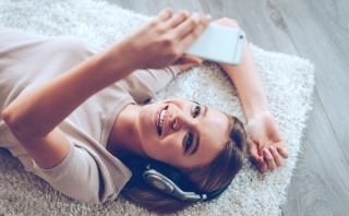 Top view of beautiful young woman in headphones making selfie while lying on carpet at home